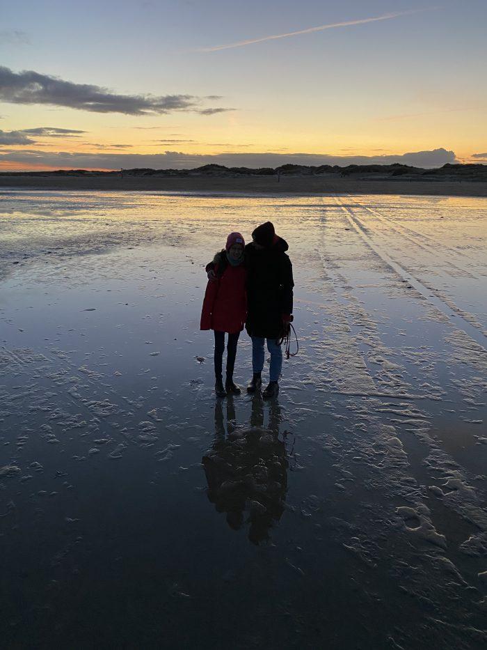 Zwei Frauen zum Sonnenaufgang am Strand in Sankt Peter Ording